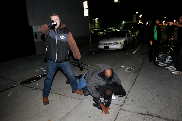 An under cover officer points his gun at the crowd while his partner subdues a protester who struck him in the back of the head, as demonstrations continue for a fifth night in Oakland, CA, on Wednesday, December 10, 2014.